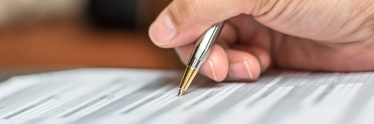 Close up shot of a person's hand holding a pen they are using to file out a form