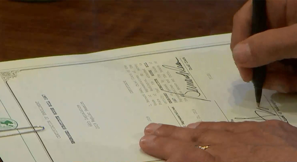 Governor's hand signs bill into law