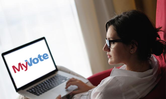 woman on couch with a laptop with the MyVote logo