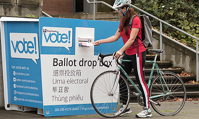a person dropping ballot in a dropbox