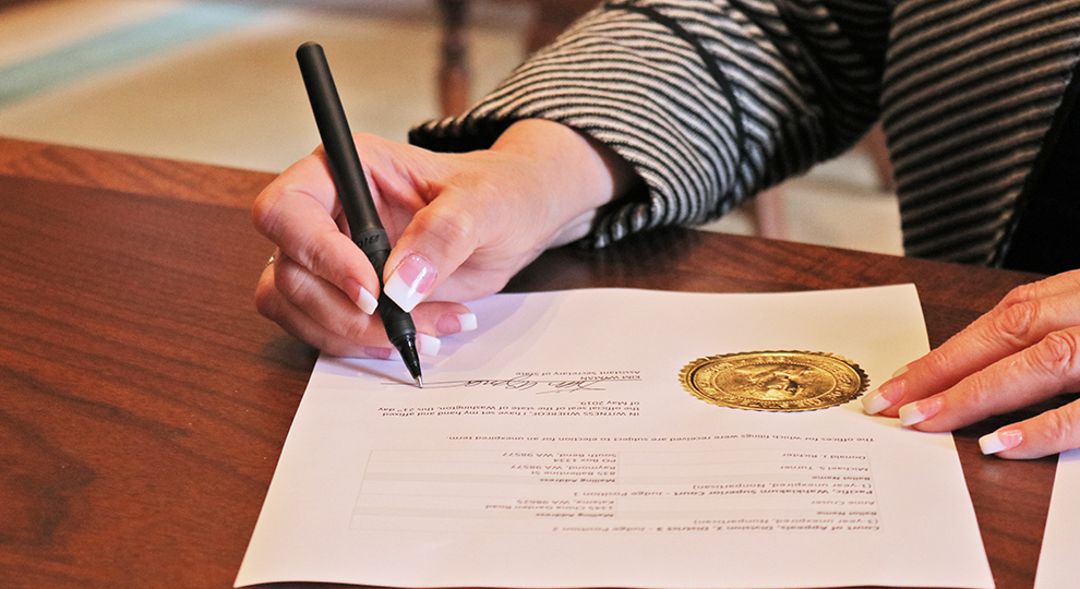 Image of Secretary Wyman's hand signing the certification for candidates for 2019 Primary