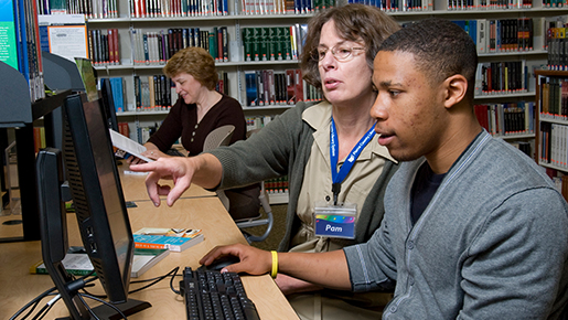 A librarian assists a young man with the computer at a local library while other patrons look on.
