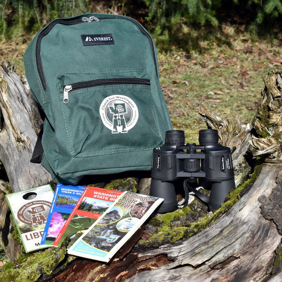 Check Out Washington backpack, binoculars, Washington Birds pamphlet, Washington Trees and Wildflowers pamphlet, a Washington State Parks guide, and Discover Pass displayed on a log
