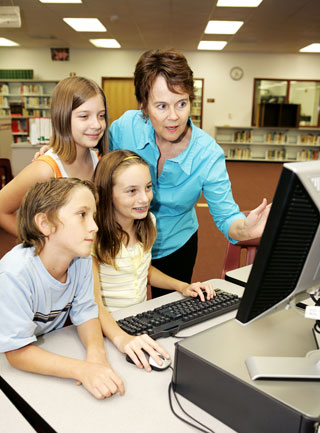 Teacher-librarian instructing kids on how to use a computer