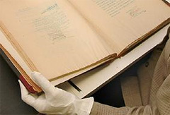 Gloved hand handling archival materials