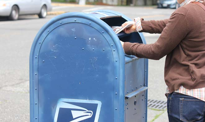 woman putting a ballot into a USPS mail box