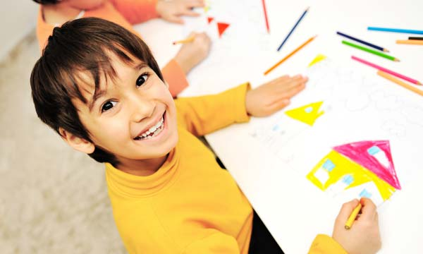 child smiling while drawing