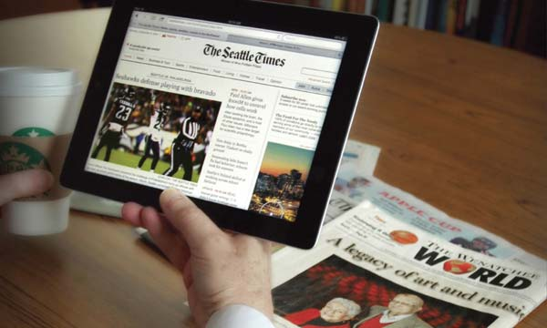 person holding a tablet with Seattle Times on the screen and Wenatchee World news on the table