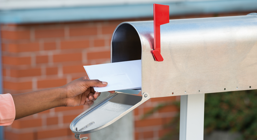 Hand putting envelope in mailbox