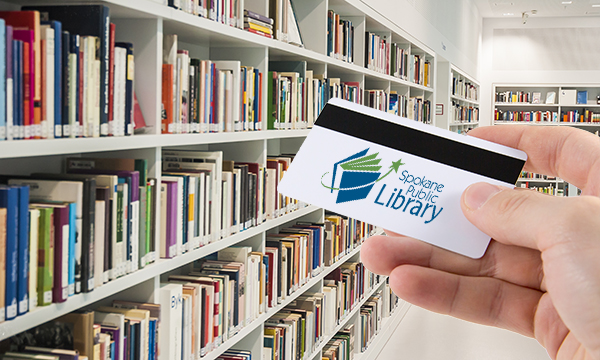 Hand holding library card with Spokane Public Library Logo