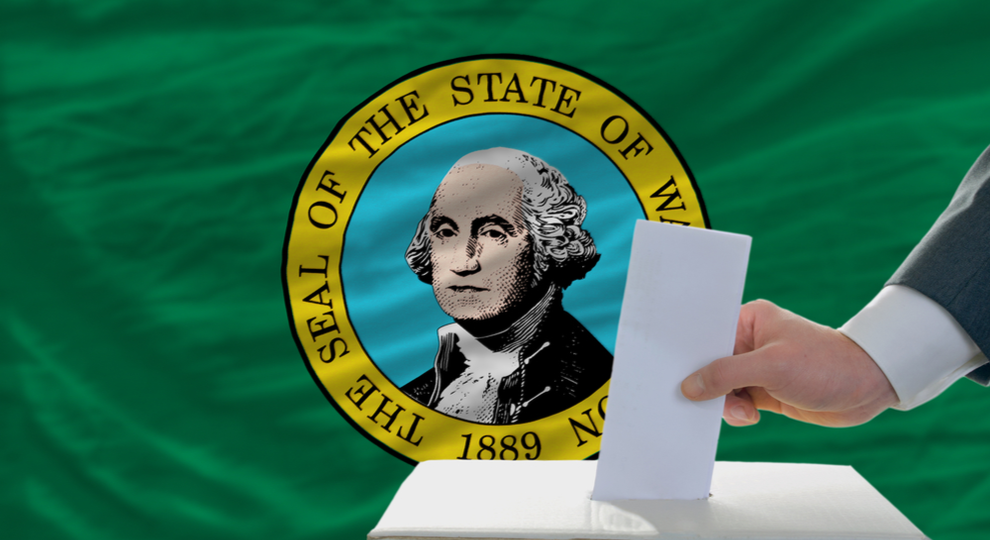 Washington State flag background with a hand putting a slip of paper into a box.